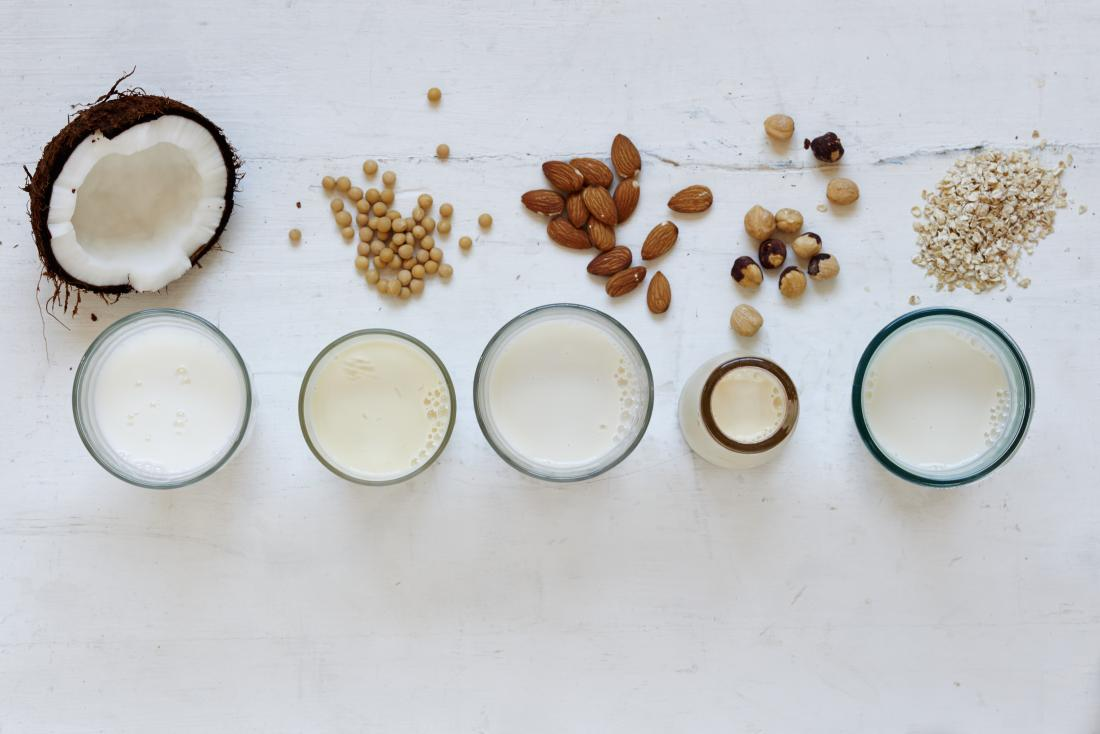 Non-dairy milk alternatives suitable for vegans including coconut, soya, almond, hazelnut, and oat milk, top down view of glasses next to their ingredient.