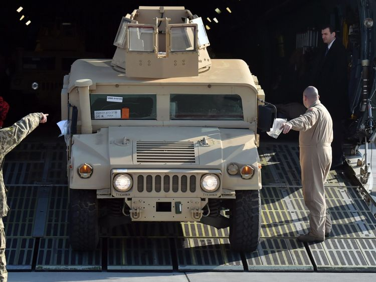 A Humvee is unloaded from a military plane