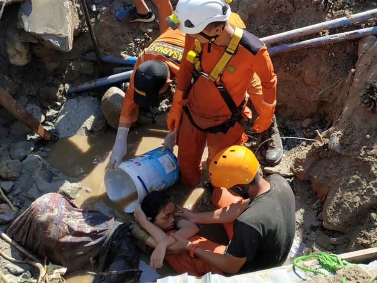Search and rescue workers help rescue a person trapped in rubble following the disaster