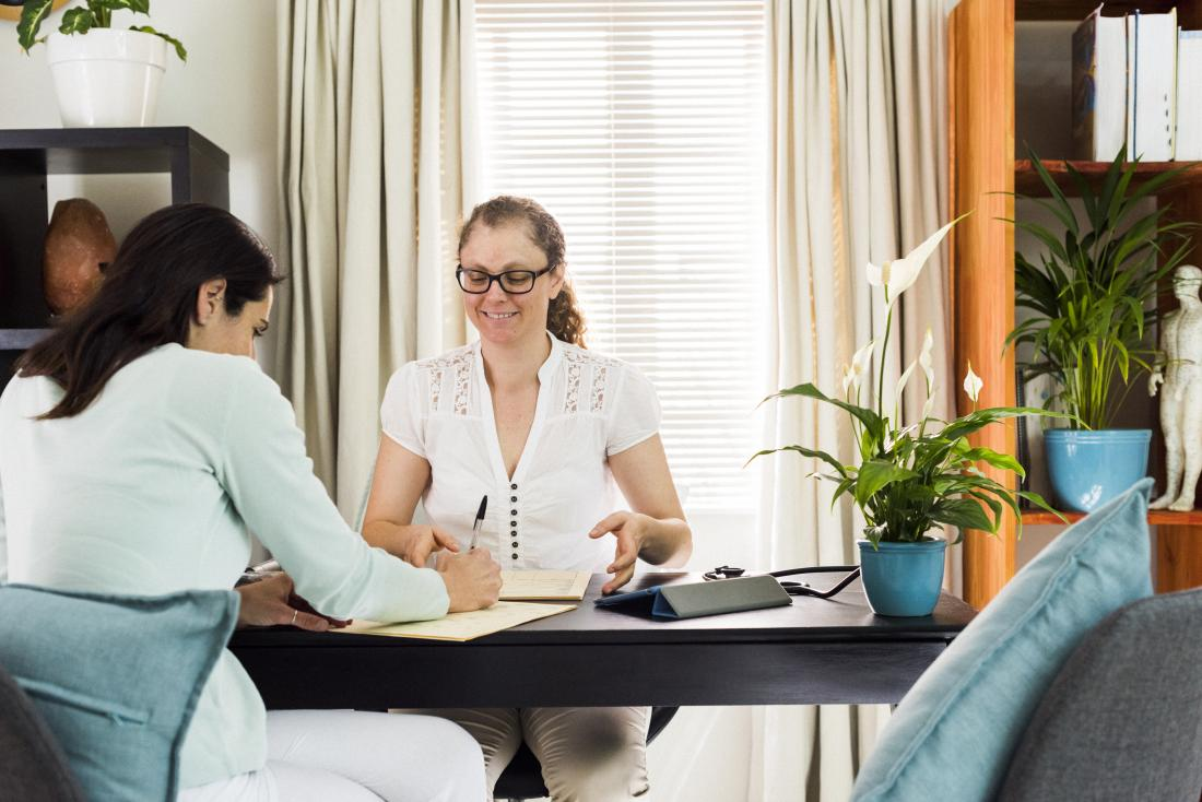Alternative therapist in office getting patient to sign documents