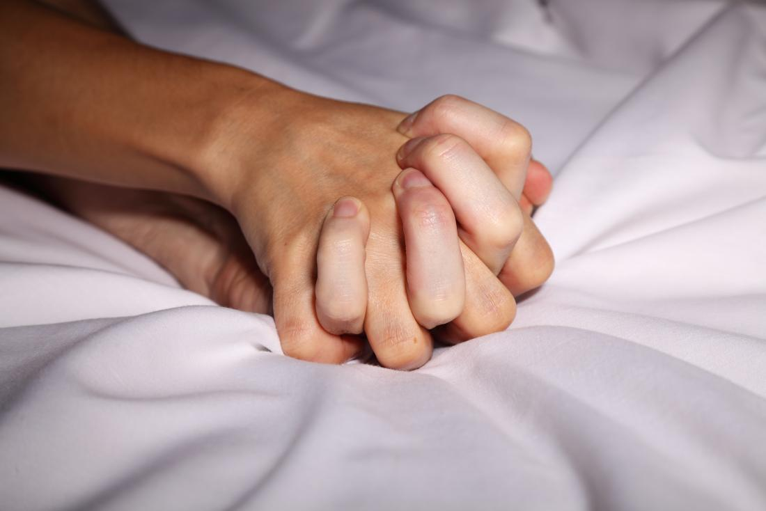 couple holding hands in bed during sex