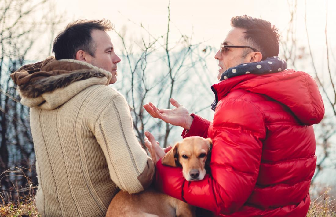 Two men talking outdoors with dog in winter coats