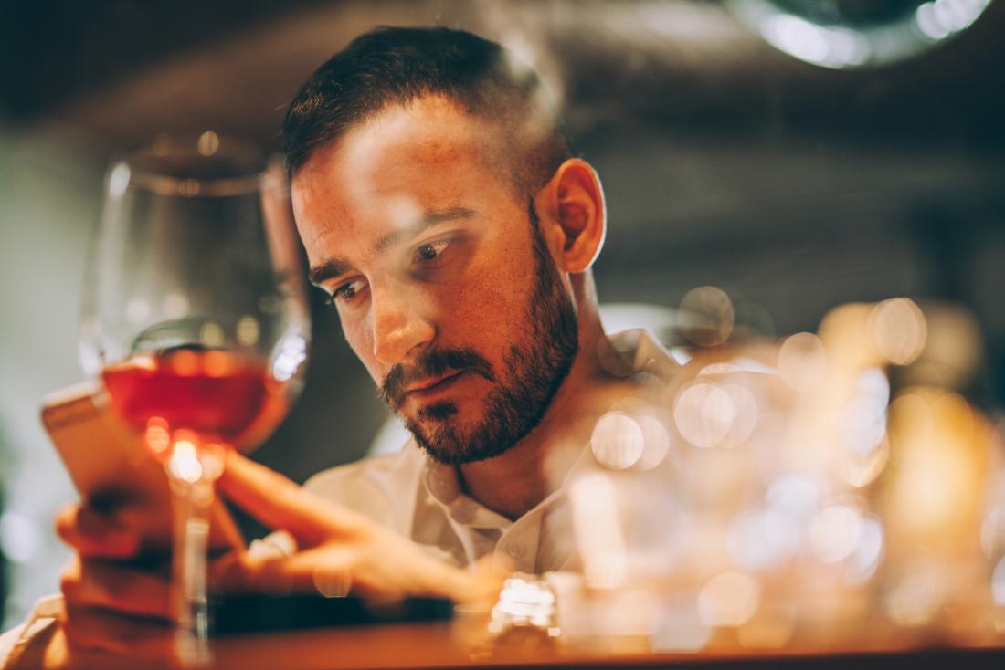 man looking sad, checking phone
