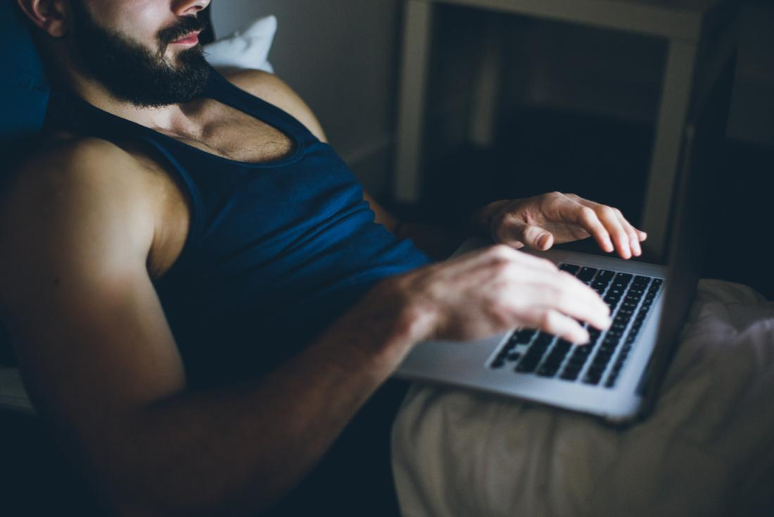 Man using his laptop in bed