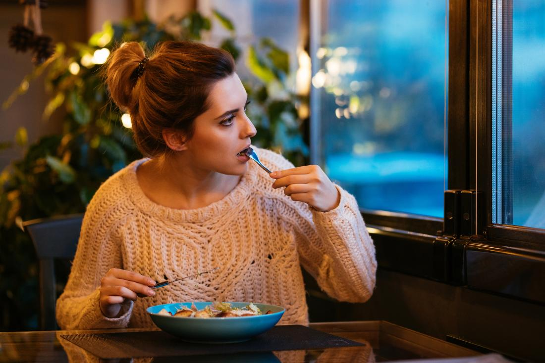 Woman eating food in restaurant looking out of window