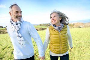 A couple hikes through a field
