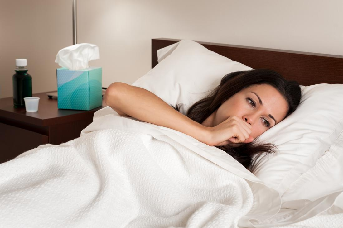 Woman in bed with the flu with difficulty breathing