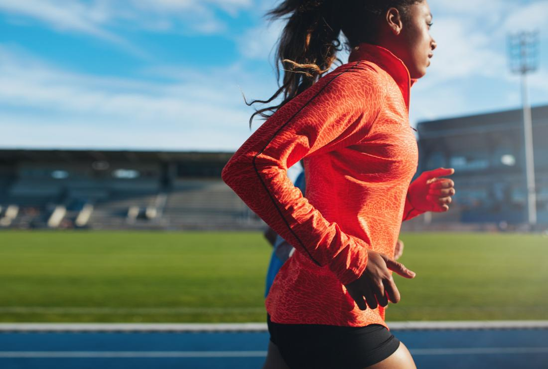 Woman using BCAAs supplement running on racing track.