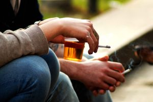 A person holding a drink and a cigarette.