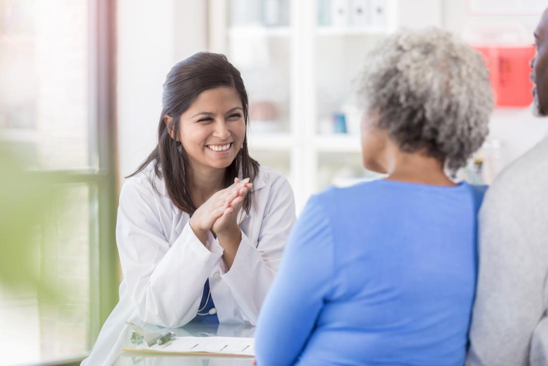 Female doctor speaking to mature senior woman