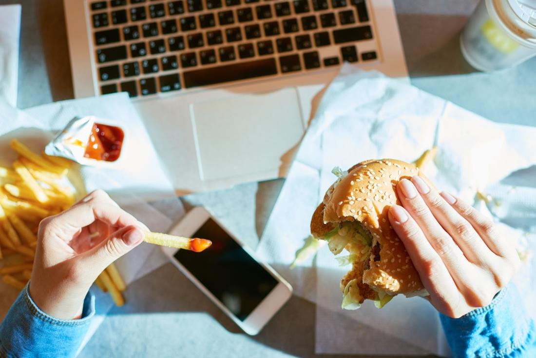 Person eating fast food burger and chips at their desk over their laptop and smartphone