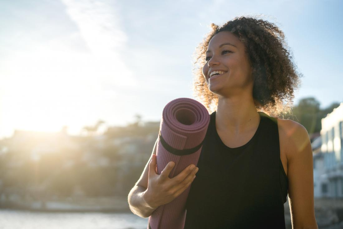 Woman smiling outdoors with yoga mat in sunshine.