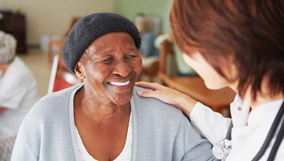 Older woman in a nursing home with a care provider's hand on her shoulder