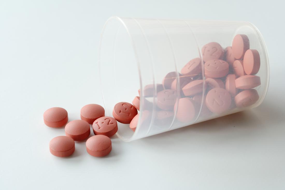 Ibuprofen pills in plastic cup