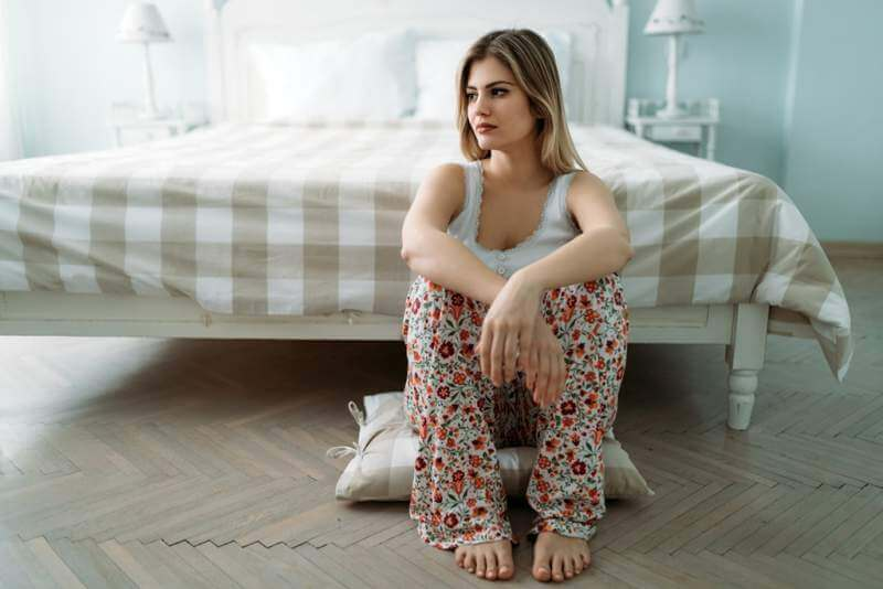 depressed-young-woman-sitting-on-bed-at-home