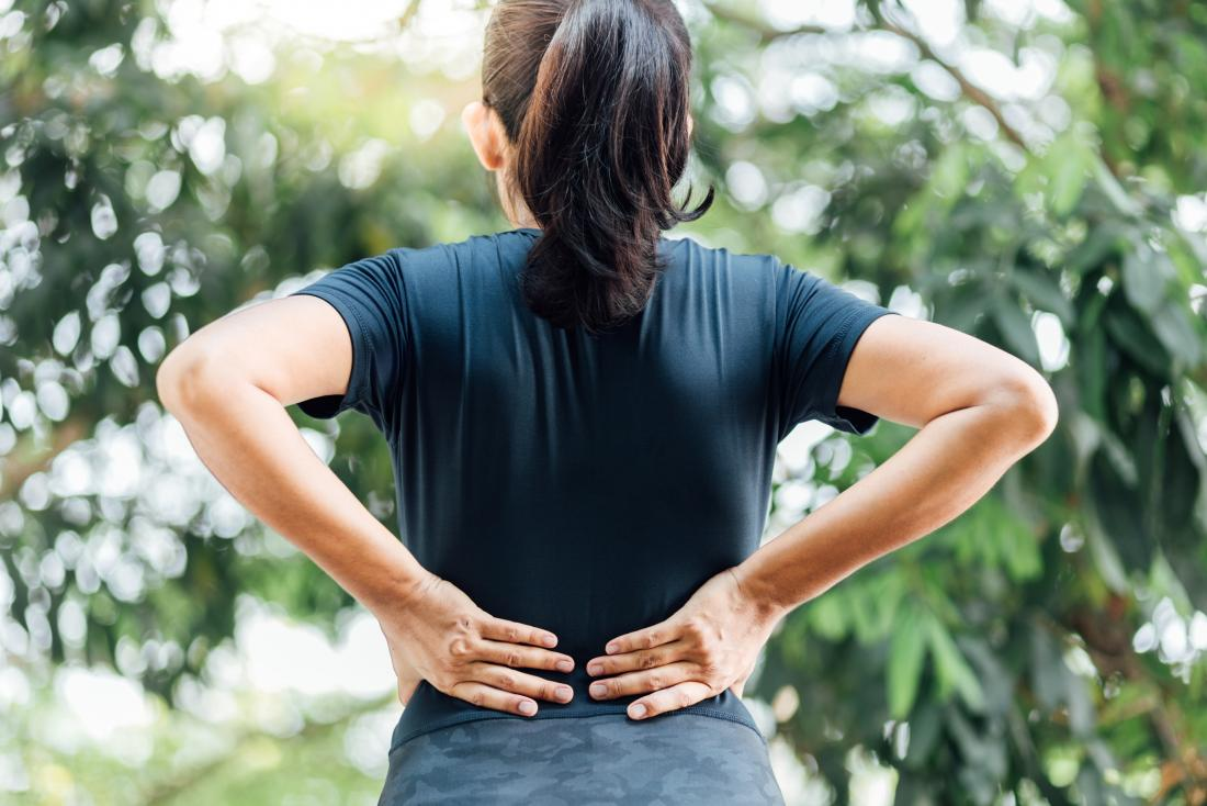 Woman holding her back due to lower back and hip pain