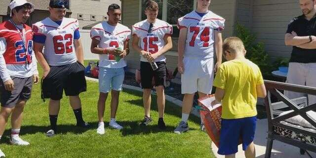 Christian Larsen opened a gift from Nampa High School Football players who attended his birthday party.