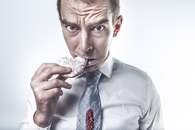 man snacking on doughnut