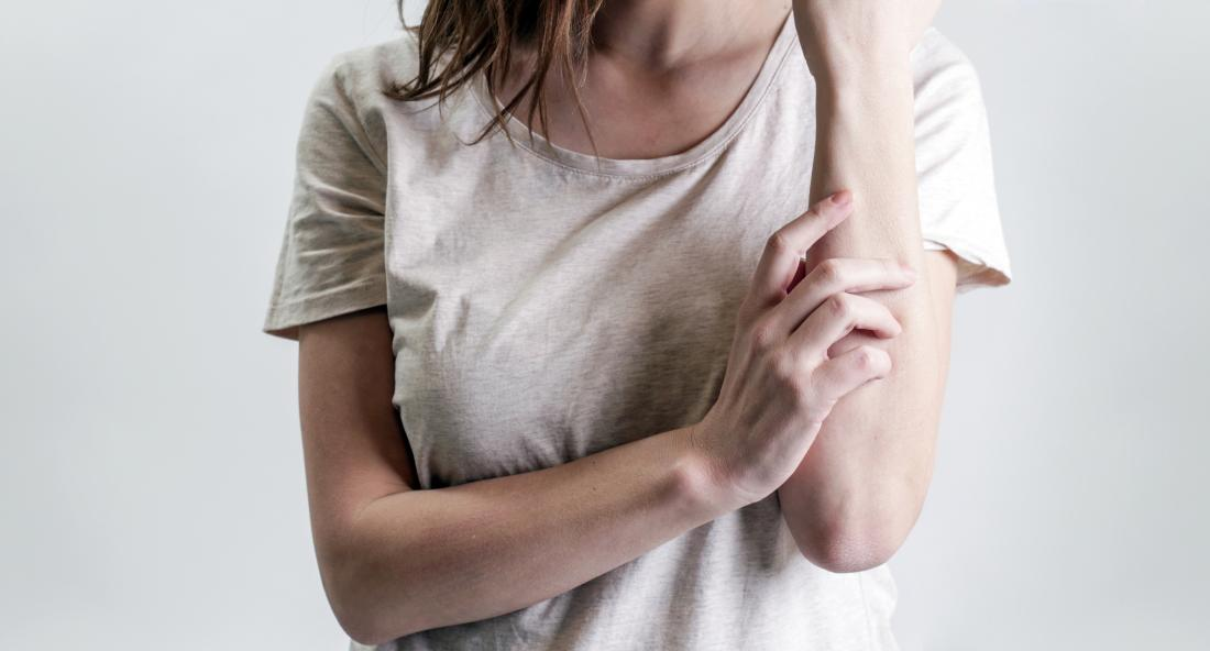 woman touching her arm