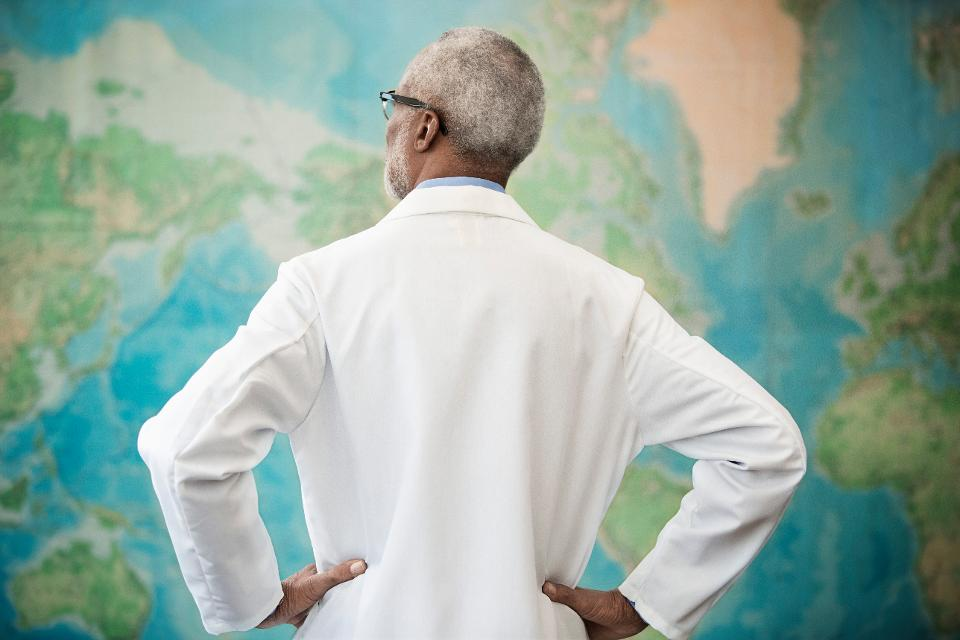 doctor examining world map in office