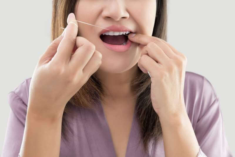 woman-flossing-teeth-with-dental-floss