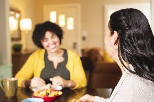 A woman with a hearing aid talks to a friend who is smiling broadly.