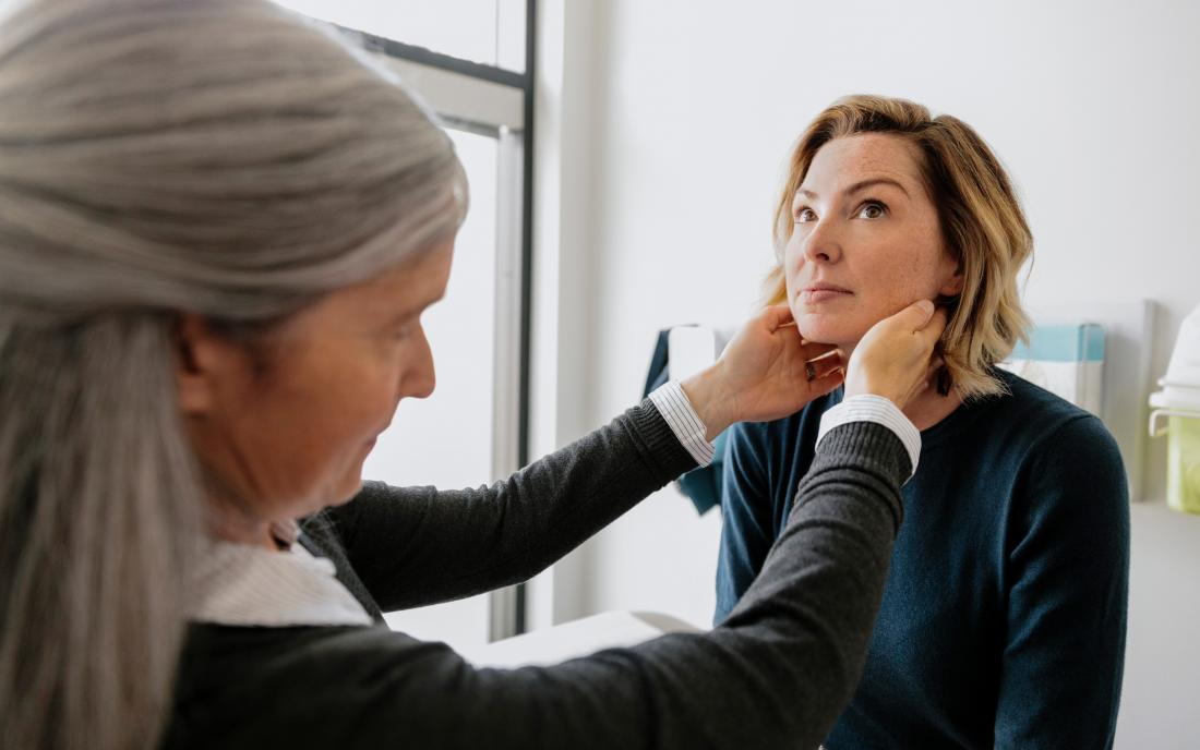 a doctor checking a womans neck for Swollen cervical lymph nodes