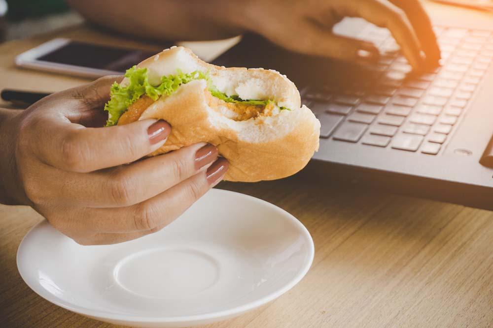 Boost energy - 5 natural ways-Boost-energy-5-natural-ways-woman-eating-unhealthy-food-at-desk