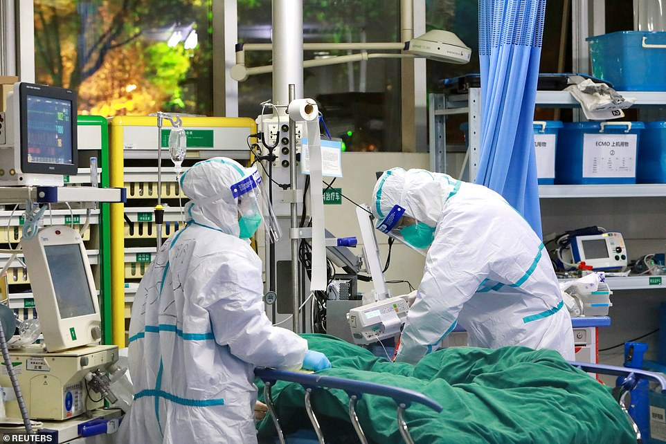 The wife, 60, had traveled to Wuhan - where the virus originated - in late December to take care of her elderly father. Pictured: Medical staff in protective suits treat a coronavirus patient at Zhongnan Hospital of Wuhan, January 28
