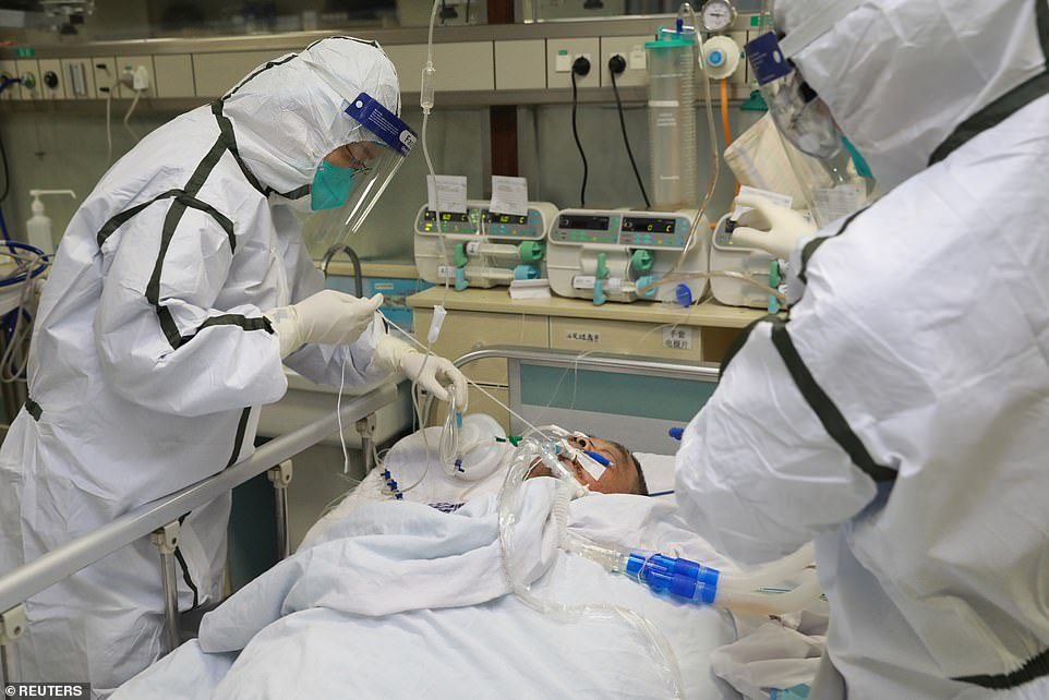 She returned to Chicago on January 13, but did not show symptoms until several days later. Pictured: Medical staff in protective suits treat a coronavirus patient at Zhongnan Hospital in Wuhan, January 27