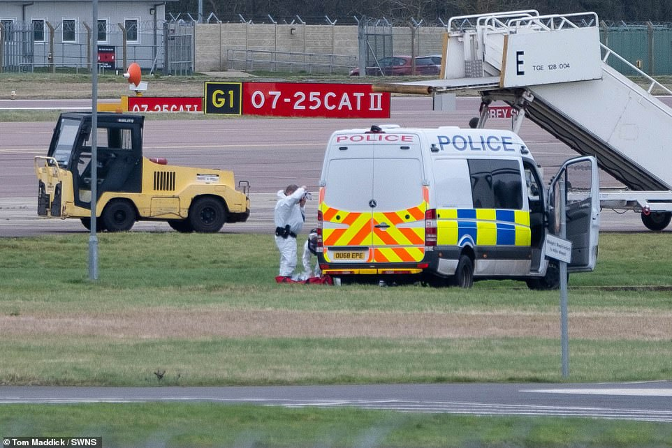 Police in hazmat suits are pictured on the runway at Brize Norton today
