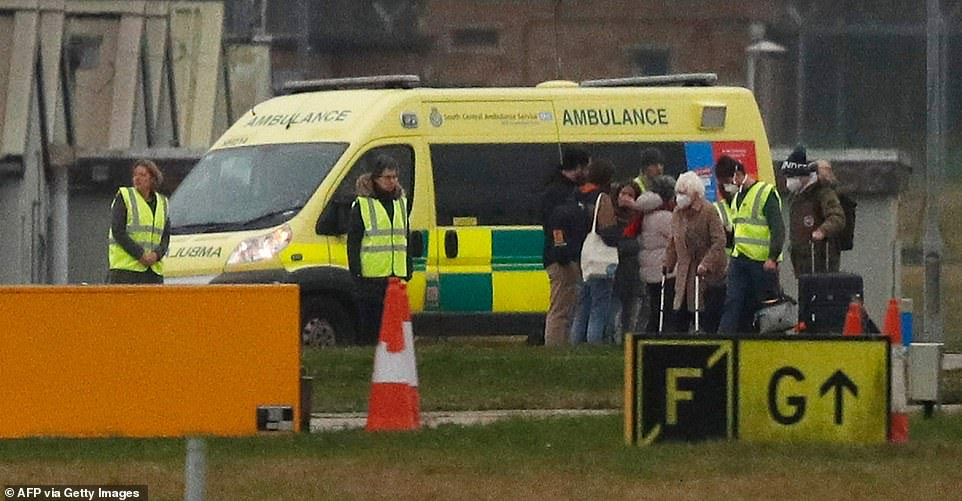 People standing beside an ambulance waiting for the passengers are seen without face masks or protective equipment of any kind
