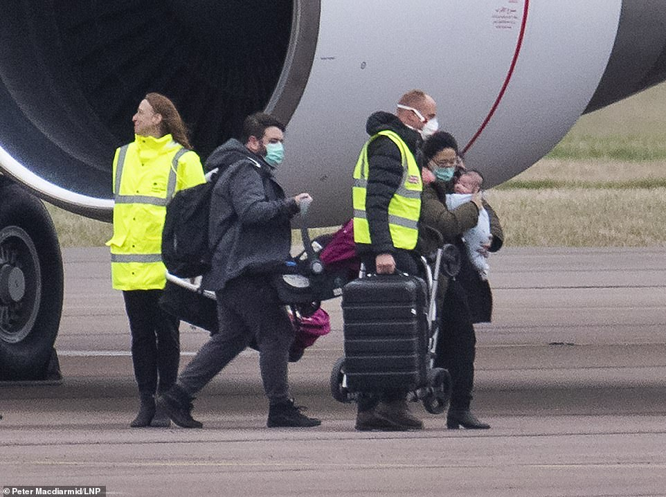 One worker standing by the plane is pictured without a mask, as passengers carrying luggage make their way across the runway to the coaches taking them to the Wirral