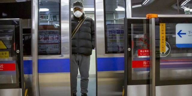 A man wearing a face mask stands on a subway train in Beijing, Monday, Feb. 3, 2020. Much of China officially went back to work on Monday after the Lunar New Year holiday was extended several days by the government due to a virus outbreak, but China's capital remained largely empty as local officials strongly encouraged non-essential businesses to remain closed or work from home. (AP Photo/Mark Schiefelbein)