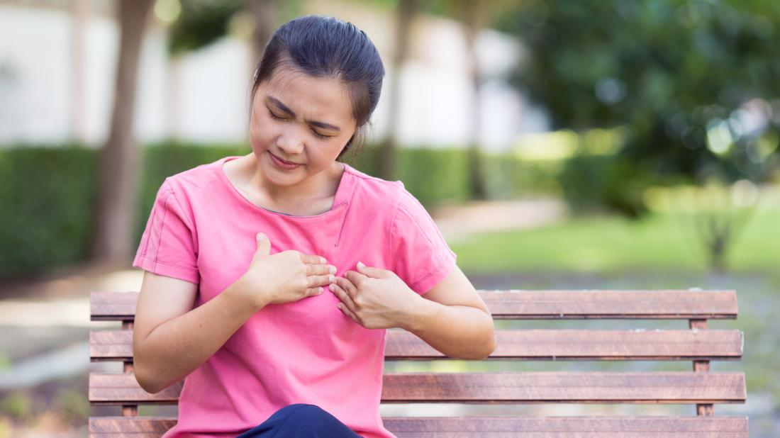 a woman sat on a bench and experiencing chest pain on left side