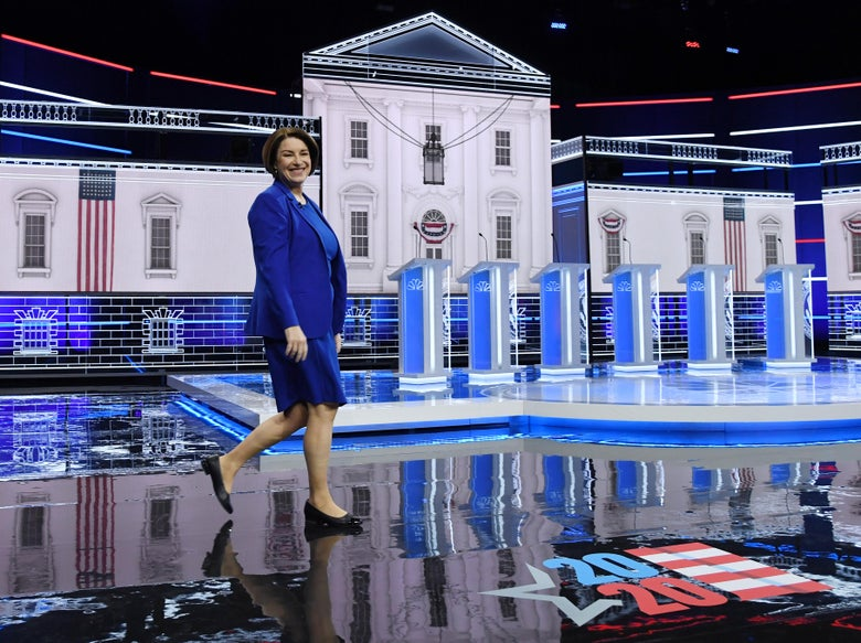 Amy Klobuchar walks across the debate stage.