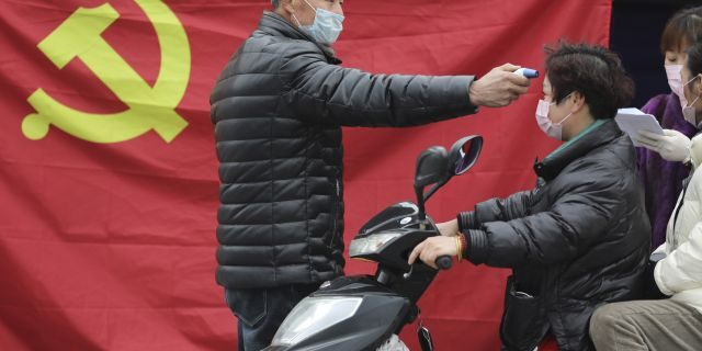 A volunteer stands in front of a Communist Party flag as he takes the temperature of a scooter driver at a roadside checkpoint in Hangzhou in eastern China's Zhejiang Province, Monday, Feb. 3, 2020. China sent medical workers and equipment to a newly built hospital, infused cash into financial markets and further restricted people's movement in sweeping new steps Monday to contain a rapidly spreading virus and its escalating impact. (Chinatopix via AP)
