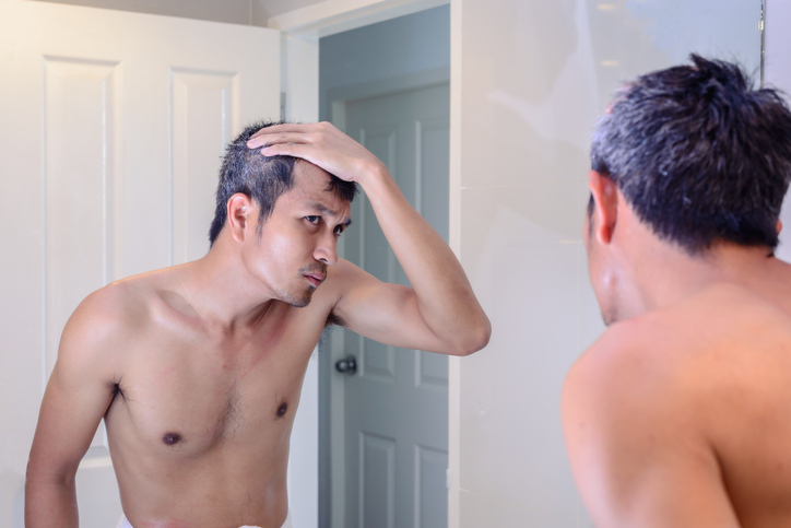 Man worried about gray hair looking into mirror