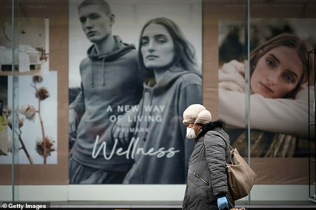 A woman wearing a mask walks past a closed shop window display during the pandemic lockdown in Manchester