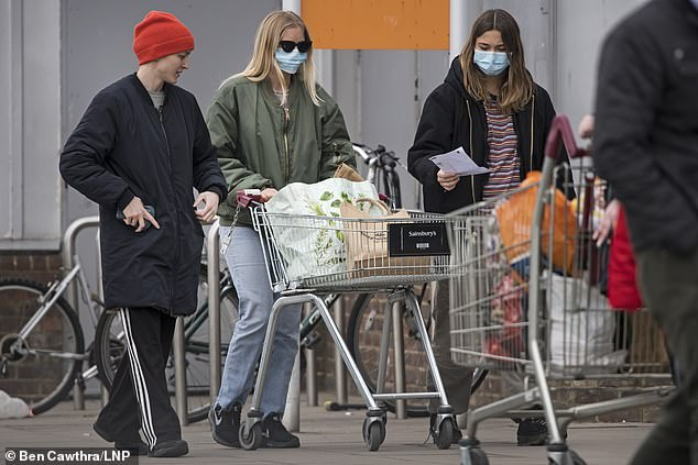 Shoppers wearing face masks queue to enter Sainsbury's supermarket on Ladbroke Grove in West London on Wednesday
