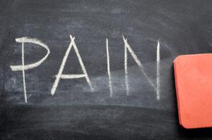 """A red eraser erasing the word """"pain"""" written in chalk"""