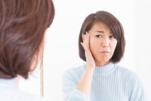 woman checking for adult acne